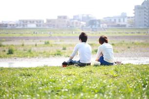 土手に座る若いカップルの写真素材 [FYI00307632]