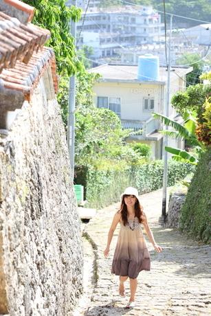 沖縄の石畳道を散歩する若い女性の写真素材 [FYI00307638]