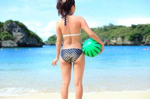 ビーチボールを持ったビキニの若い女性と海の写真素材 [FYI00307641]