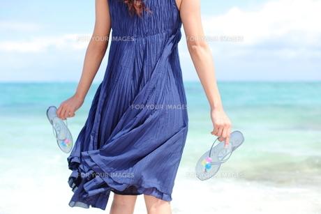 沖縄の海でサンダルを持ちたたずむ若い女性の写真素材 [FYI00307642]
