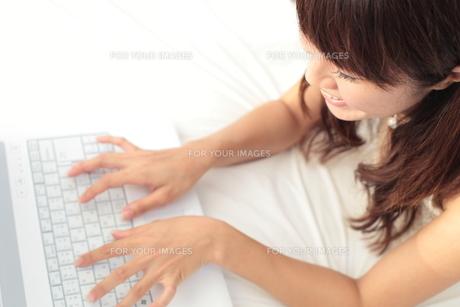 ベッドの上でパソコンをする女性の写真素材 [FYI00307644]