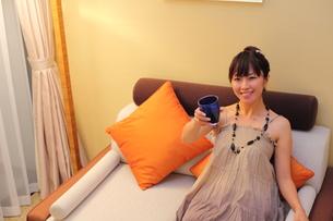 グラスをもちソファでくつろぐ笑顔の20代女性の写真素材 [FYI00307645]