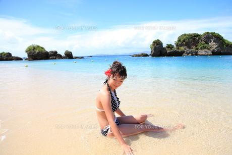 波と戯れる笑顔の若い女性の写真素材 [FYI00307646]