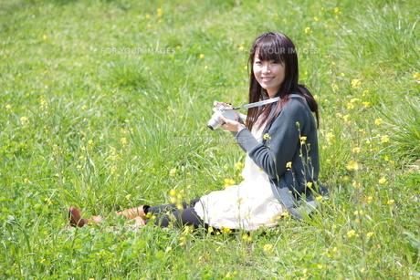 カメラを持つ笑顔の若い女性の写真素材 [FYI00307649]