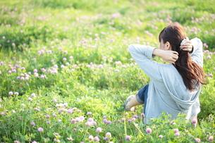 草原の中でたたずむ若い女性の写真素材 [FYI00307653]