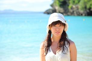 沖縄の海辺にたたずむ笑顔の若い女性の写真素材 [FYI00307663]