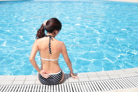プールサイドでくつろぐ水着姿の20代女性の写真素材 [FYI00307665]