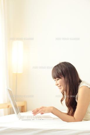 ベットの上でパソコンをする女性の写真素材 [FYI00307679]