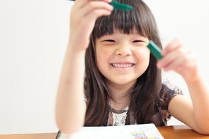 ペンをもつ笑顔の女の子の写真素材 [FYI00307684]
