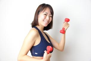 ダンベルを持つ笑顔の若い女性の写真素材 [FYI00307690]