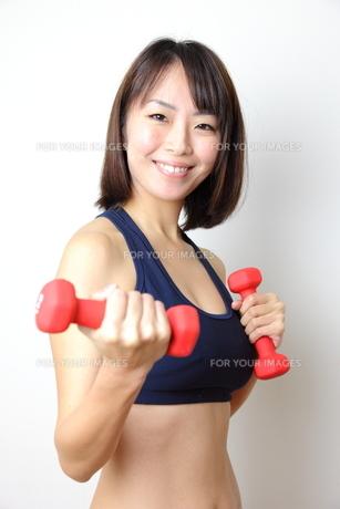ダンベルダイエットをする笑顔の若い女性の写真素材 [FYI00307697]