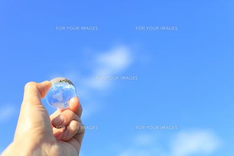 青空とガラスの地球儀を持つ男性の手の素材 [FYI00307713]