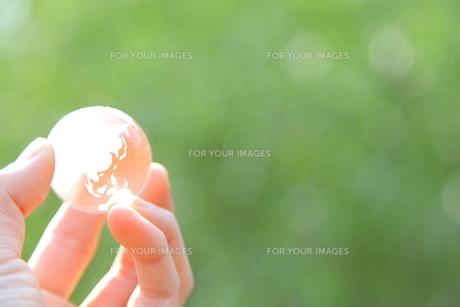 ガラスの地球儀を掴む女性の手の素材 [FYI00307716]