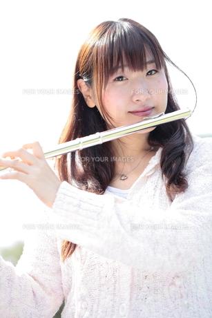 フルートを吹く笑顔の若い女性の写真素材 [FYI00307718]