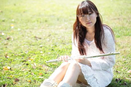 芝生に座りフルートを持つ女性の写真素材 [FYI00307727]