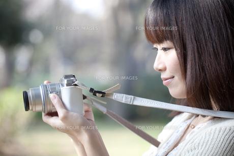 カメラを持つ笑顔の若い女性の写真素材 [FYI00307787]