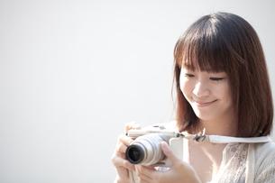 カメラを持つ笑顔の若い女性の写真素材 [FYI00307842]