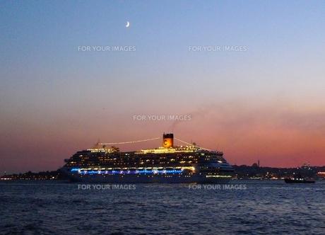 三日月のかかる夕暮れのトルコのイスタンブール港を出航する客船の写真素材 [FYI00312346]