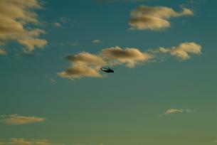 夕暮れの空を飛ぶヘリの写真素材 [FYI00315897]
