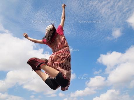 ジャンプする女性の後ろ姿の写真素材 [FYI00317051]