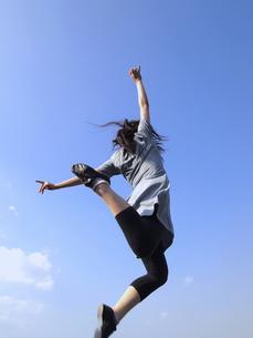 青空にジャンプする女性の写真素材 [FYI00317075]