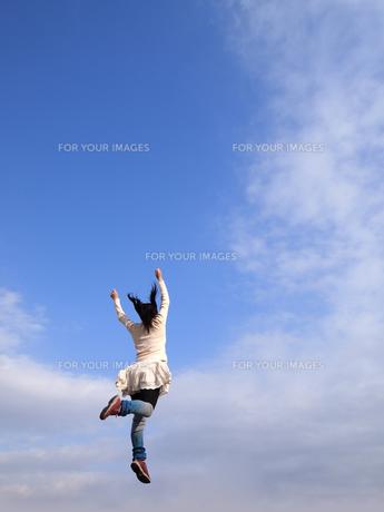 青空にジャンプする女性の写真素材 [FYI00317163]