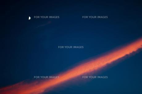 夕焼けに染まる一筋の雲、ひっそりと佇む半月の素材 [FYI00318245]