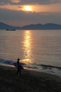 夕焼けの海とサーファーの写真素材 [FYI00319820]