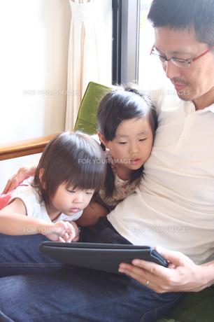 タブレットPCを覗き込む姉妹の写真素材 [FYI00325195]