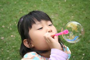 公園でシャボン玉をして遊ぶ女の子の素材 [FYI00325236]