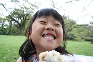 公園でおにぎりを食べる女の子の写真素材 [FYI00325246]