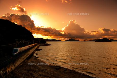 瀬戸内海に沈む夕日を瀬に走る特急しおかぜ号の写真素材 [FYI00329301]
