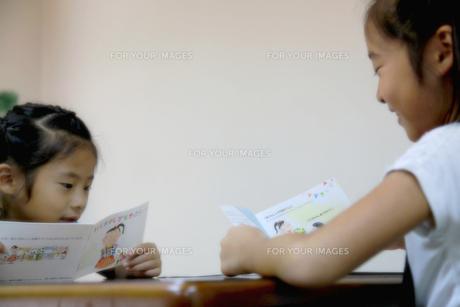 仲良く絵本を見る姉妹の写真素材 [FYI00333750]