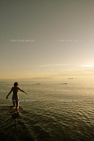 夕焼けの海で遊ぶ若い女性の写真素材 [FYI00333889]