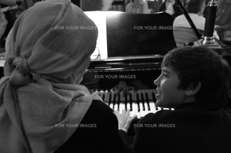 孫と一緒にピアノを弾く祖母の写真素材 [FYI00333896]