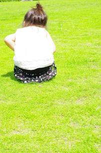 公園の広場に座る女の子の後ろ姿の写真素材 [FYI00335663]