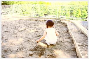 砂場で遊ぶ女の子の後ろ姿の写真素材 [FYI00335684]
