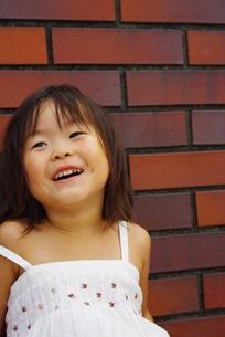 ブロック塀で笑ってる女の子の写真素材 [FYI00335686]