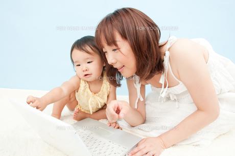 パソコンの画面を見る親子の写真素材 [FYI00336481]