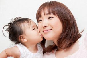 お母さんの頬にキスする娘の写真素材 [FYI00336506]