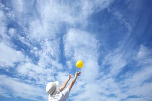 青空と黄色いボールと女性の写真素材 [FYI00368212]