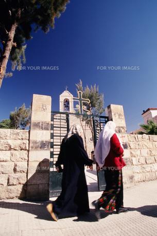 ギリシャ正教会前を通るアラビア衣装の女性たちの写真素材 [FYI00368441]