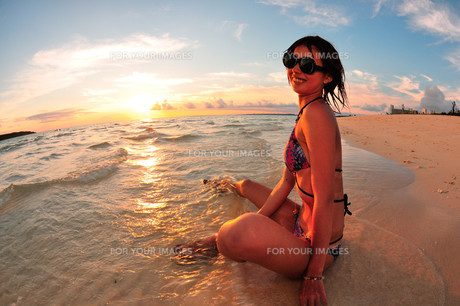 宮古島/前浜ビーチの夕景と若い女性の素材 [FYI00371353]