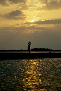 夕陽と釣りをする子供の写真素材 [FYI00377949]