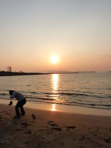 夕日と男性がメッセージを書く光景の写真素材 [FYI00378844]