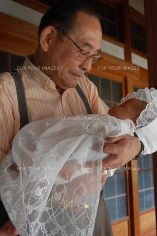 孫のお宮参りで微笑むおじいちゃんの写真素材 [FYI00379570]