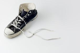 紐の解けたボロボロの運動靴のアップの写真素材 [FYI00381378]