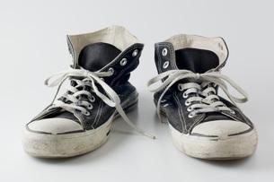 白背景にボロボロの運動靴のアップの写真素材 [FYI00381381]