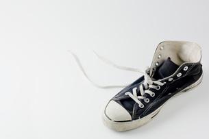白背景にぼろぼろの片足の運動靴のアップの写真素材 [FYI00381386]