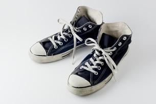白背景にボロボロの運動靴のアップの写真素材 [FYI00381393]